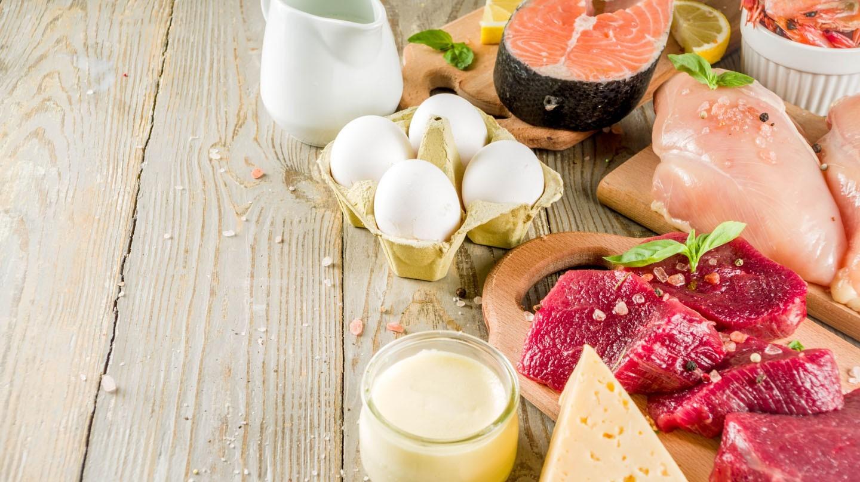 Vitamin B12: Fleisch, Fisch, Eier, Käse und Joghurt auf einem Holztisch angerichtet.